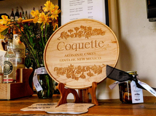 Coquette logo wooden sign on bar at Read Street tasting room